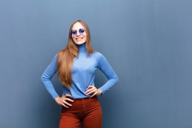Jonge mooie vrouw met zonnebril blauwe muur met een kopie ruimte