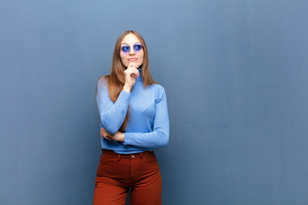 Jonge mooie vrouw met zonnebril op blauwe muur met een exemplaarruimte