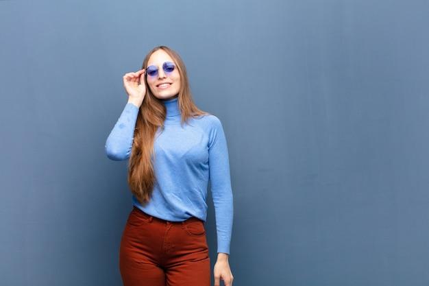 Jonge mooie vrouw met zonnebril tegen blauwe muur met een exemplaarruimte