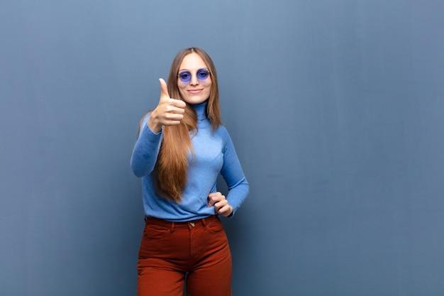 Jonge mooie vrouw met zonnebril tegen blauwe muur
