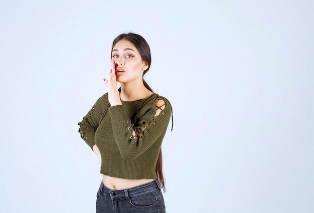 Jonge mooie vrouw model fluisteren iets tijdens het kijken naar de camera.