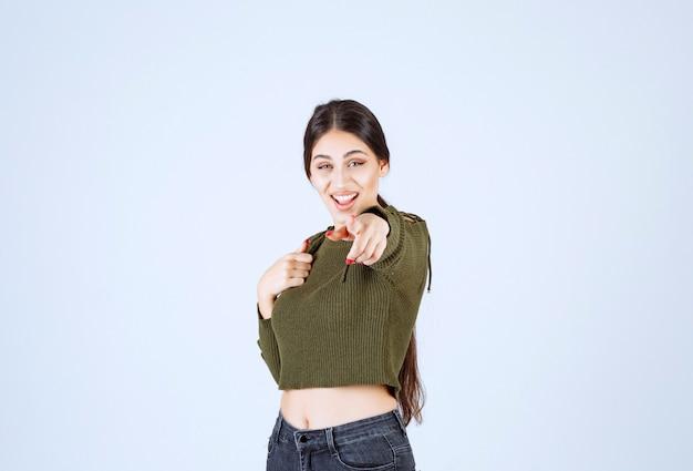 Jonge mooie vrouw model permanent en wijzend op de camera.