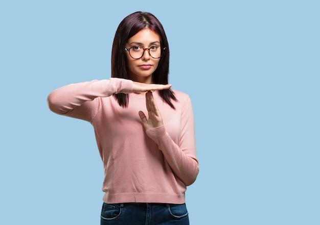Jonge mooie vrouw moe en verveeld, het maken van een time-out gebaar, moet stoppen vanwege werkstress, tijd concept