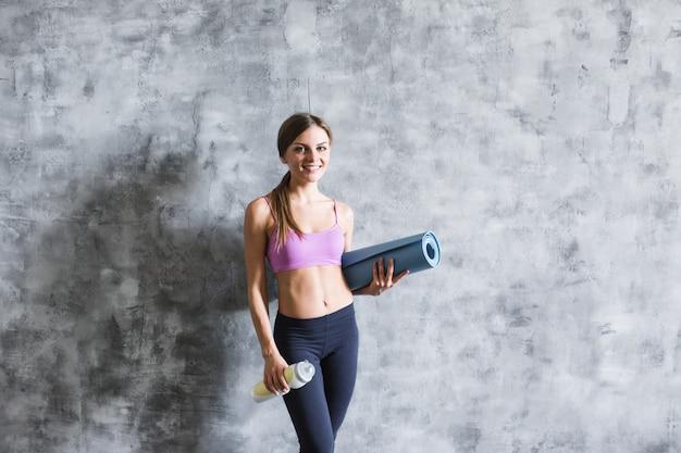 Jonge mooie vrouw na training met een fles en yoga mat.