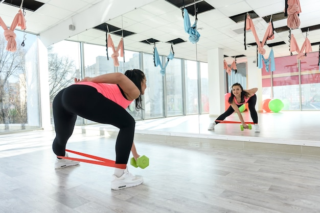 Jonge mooie vrouw oefening training elastische bandage sportschool. gezondheidstraining