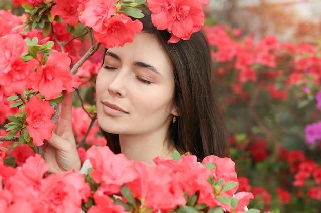 Jonge mooie vrouw onder roze bloemen, vrouwelijk portret