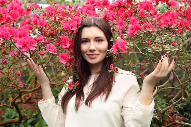 Jonge mooie vrouw onder roze bloemen