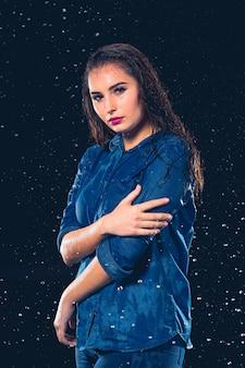 Jonge mooie vrouw onder scheutje regen