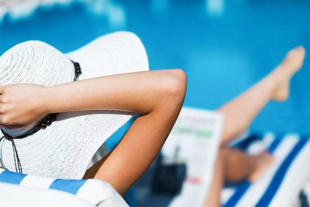 Jonge mooie vrouw ontspannen in de buurt van pool