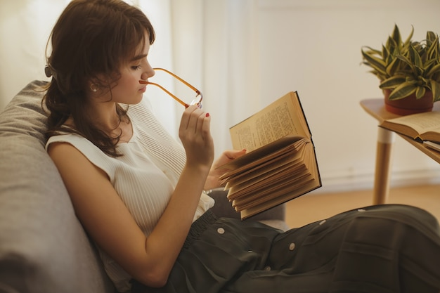 Jonge mooie vrouw ontspannen thuis in de gezellige avond en leesboek.