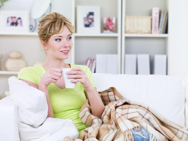 Jonge mooie vrouw op de bank met kop verwarmende drank - binnenshuis