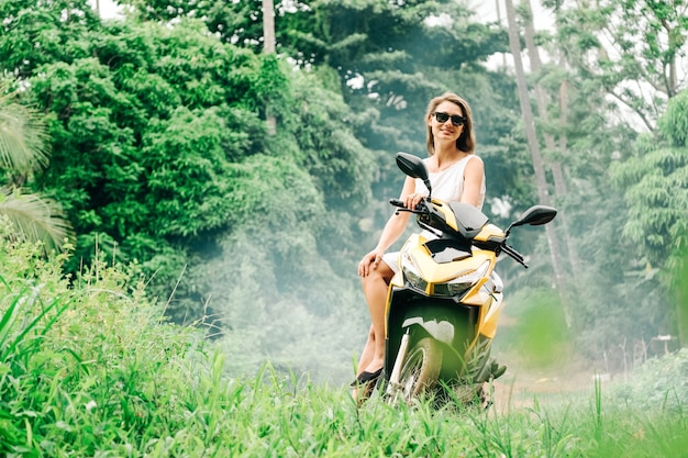 Jonge mooie vrouw op de scooter