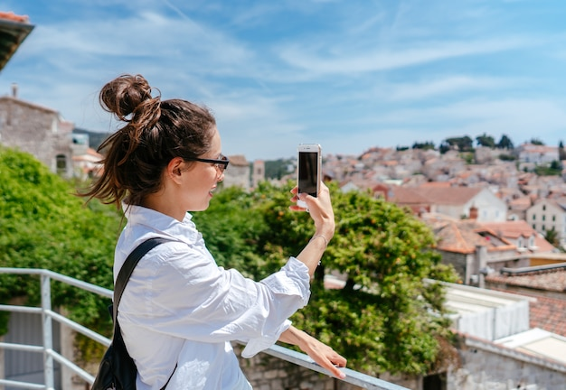 Jonge mooie vrouw op een balkon met uitzicht op een kleine stad in kroatië