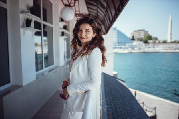 Jonge mooie vrouw op een balkoncafé. wachten op zakelijke bijeenkomst