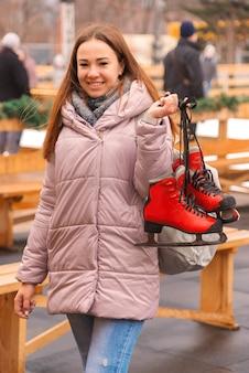 Jonge mooie vrouw op een ijsbaan met schaatsen in haar handen