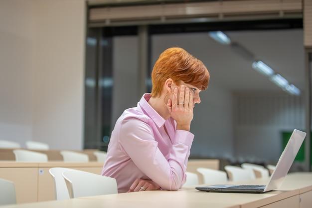 Jonge mooie vrouw op een universitaire lezing die aan laptop werkt
