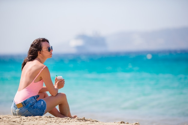 Jonge mooie vrouw op het strand in europa. meisje met koffie op vakantie in mykonos, griekenland