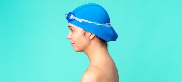 Jonge mooie vrouw op profielweergave denken, verbeelden of dagdromen met zwembril