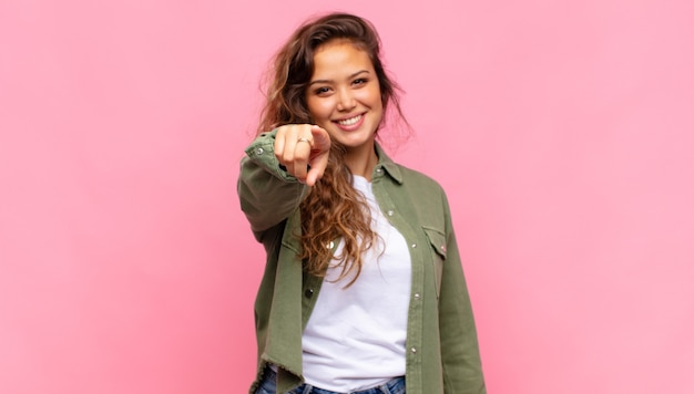 Jonge mooie vrouw op roze achtergrond direct wijzen