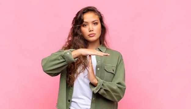 Jonge mooie vrouw op roze achtergrond. time-out gebaar