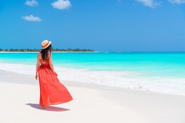 Jonge mooie vrouw op tropische kust. achteraanzicht van een jong meisje in een rode jurk