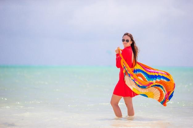 Jonge mooie vrouw op tropische kust. gelukkig meisje op mooie kledingsachtergrond het overzees