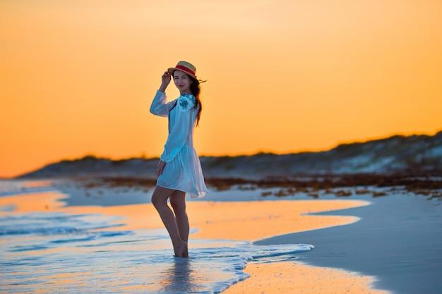 Jonge mooie vrouw op tropische kust in zonsondergang. gelukkig meisje in jurk in de avond op het strand