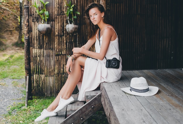 Jonge mooie vrouw op tropische vakantie in azië, zomerstijl, witte boho-jurk, sneakers, digitale fotocamera, reiziger, strooien hoed, glimlachen, boho