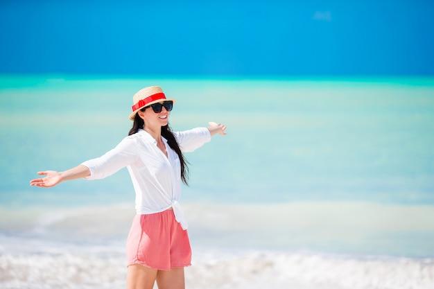 Jonge mooie vrouw op wit zand tropisch strand. blanke meisje met hoed achtergrond de zee