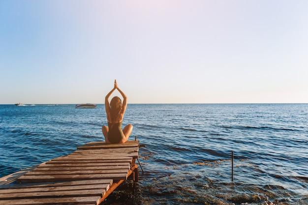 Jonge mooie vrouw op yoga op het strand