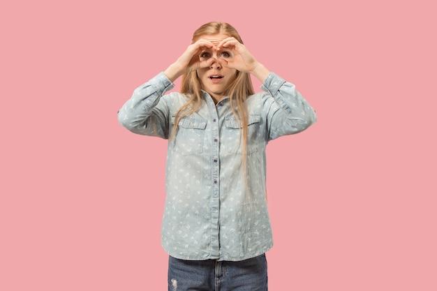 Jonge mooie vrouw op zoek in de verte en op zoek naar denkbeeldige verrekijker bij roze studio