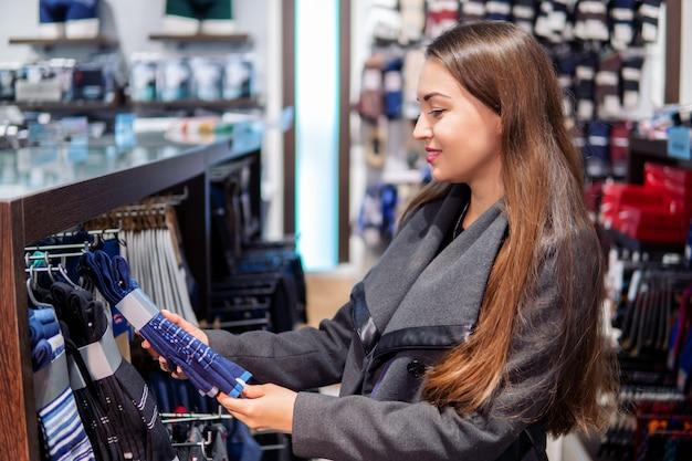 Jonge mooie vrouw op zoek naar kleding voor cadeau in een winkel supermarkt winkel
