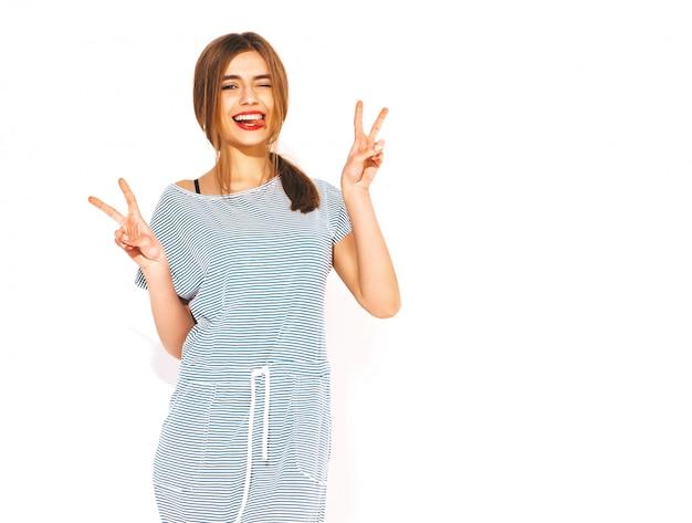 Jonge mooie vrouw op zoek. trendy meisje in casual zomer gestreepte jurk. positief grappig model. tong en vredesteken tonen