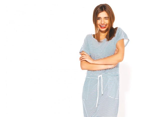 Jonge mooie vrouw op zoek. trendy meisje in casual zomer gestreepte jurk. positief grappig model. tong tonen en knipogen