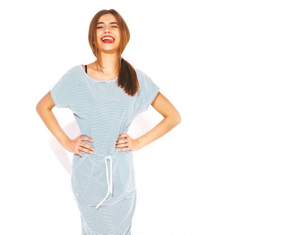 Jonge mooie vrouw op zoek. trendy meisje in casual zomer gestreepte jurk. positief grappig model. tong tonen