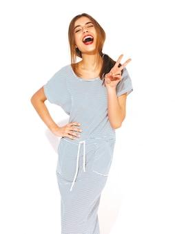 Jonge mooie vrouw op zoek. trendy meisje in casual zomer gestreepte jurk. positief grappig model. vredesteken tonen