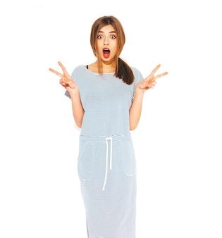 Jonge mooie vrouw op zoek. trendy meisje in casual zomer gestreepte jurk. positief grappig model