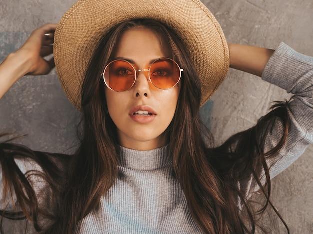 Jonge mooie vrouw op zoek. trendy meisje in casual zomer overall kleding en hoed.