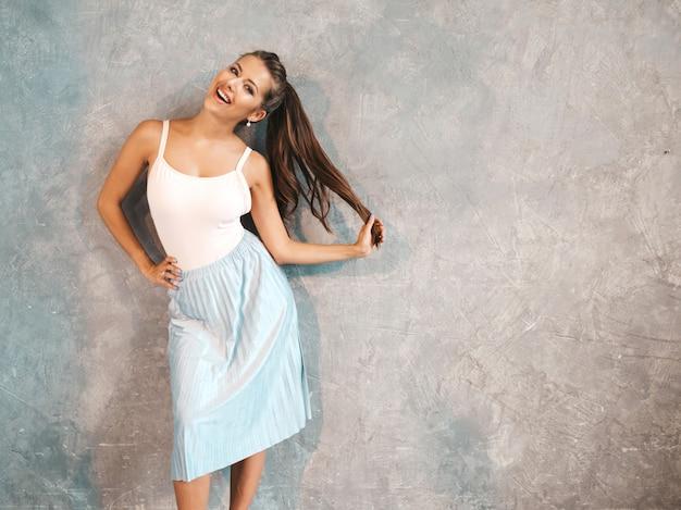 Jonge mooie vrouw op zoek. trendy meisje in casual zomerjurk. en kus geven. spelen met haar