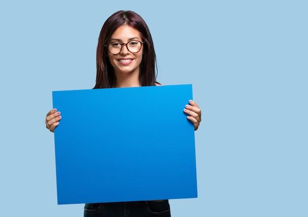 Jonge mooie vrouw opgewekt en gemotiveerd, toont een lege poster waar u een bericht kunt tonen