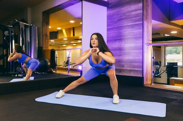 Jonge mooie vrouw opwarmt en strekt zich uit in de sportschool, op een mat in de buurt van de spiegel, in een blauw pak