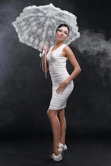 Jonge mooie vrouw over de volledige lengte in witte jurk met witte paraplu op een grijze achtergrond
