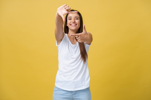 Jonge mooie vrouw over geïsoleerd geel achtergrond glimlachend makend frame