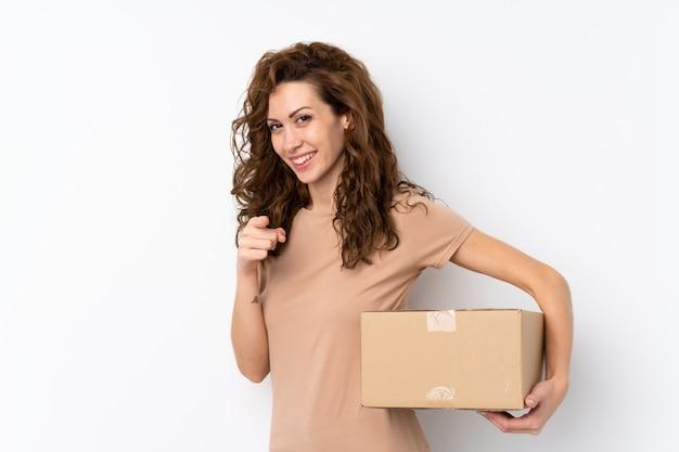 Jonge mooie vrouw over geïsoleerd houdend een doos om het naar een andere plaats te verplaatsen terwijl het richten naar de voorzijde
