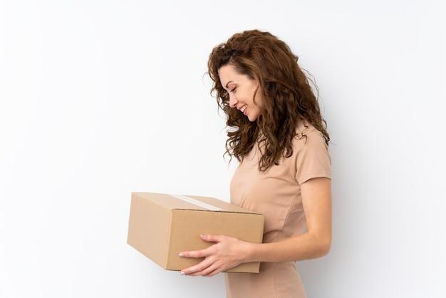 Jonge mooie vrouw over geïsoleerd houdend een doos om het naar een andere plaats te verplaatsen