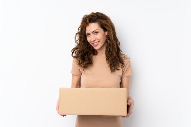 Jonge mooie vrouw over geïsoleerde muur die een doos houdt om het naar een andere plaats te verplaatsen