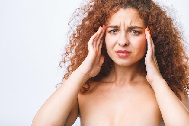 Jonge mooie vrouw over geïsoleerde over witte achtergrond die aan hoofdpijn lijdt