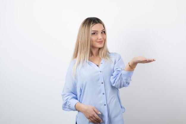 Jonge mooie vrouw permanent en poseren op witte muur.