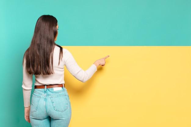 Jonge mooie vrouw permanent en wijst naar bezwaar op kopie ruimte, achteraanzicht. kopieer ruimte om uw concept te plaatsen