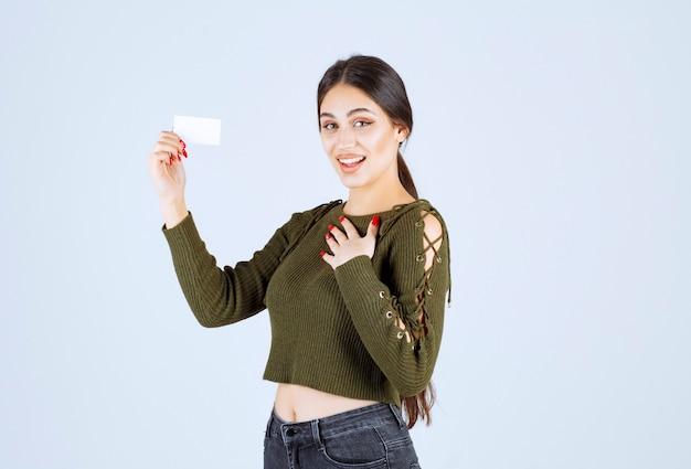 Jonge mooie vrouw permanent met blanco visitekaartje op witte achtergrond.